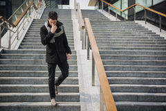 Trendy handsome young man in winter fashion standing on a long staircase Stock Photography