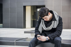 Trendy handsome young man in winter fashion using cell phone sitting Stock Image