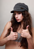 Trendy happy girl in cap showing thumb up Stock Images