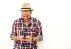 Trendy happy guy with hat looking at mobile phone Stock Image
