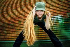 Trendy happy young woman with long blond hair. Happy girl with long blond hair - brick wall as background Stock Photo