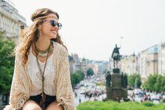 Trendy hippie woman tourist relaxing on stone parapet in Prague. Smiling trendy hippie brunette woman tourist relaxing on stone parapet on Wenceslas Square in Stock Photography