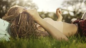 Trendy hipster girl with dreads relaxing on the grass in park. Summer lifestyle portrait of hipster woman laying on the. Grass, enjoying nice day, wearing stock footage