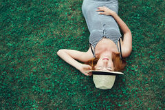 Trendy Hipster Girl Relaxing on the Grass. Young fashion trendy hipster girl in dress relaxing on the grass outdoors Royalty Free Stock Images
