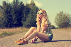 Trendy Hipster Girl Sitting on the Road Royalty Free Stock Image