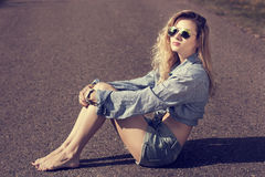 Trendy Hipster Girl Sitting on the Road. Toned Photo. Modern Youth Lifestyle Concept stock images