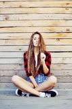Trendy hipster girl sitting on the wooden porch Royalty Free Stock Photo