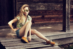 Trendy Hipster Girl Sitting on the Wooden Porch Royalty Free Stock Photos