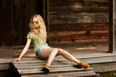 Trendy Hipster Girl Sitting on the Wooden Porch Stock Photos