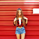Trendy hipster girl standing near red wall Stock Photography