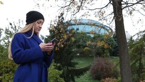 Trendy hipster girl texting on phone in autumn stock video footage