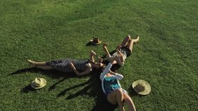 Trendy Hipster Girls Relaxing on the Grass . Summer lifestyle portrait of three hipster women laying on the grass enjoy stock video footage