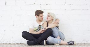 Trendy hipster young couple in love. Relaxing on a sidewalk leaning against a white wall in a close embrace enjoying a quiet moment stock video footage