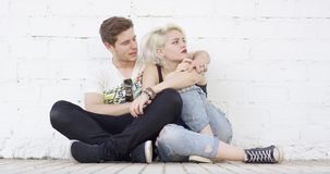 Trendy hipster young couple in love. Relaxing on a sidewalk leaning against a white wall in a close embrace enjoying a quiet moment stock footage