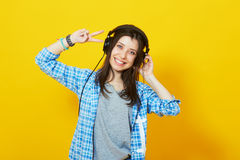 Trendy hipster young woman with headphones. Young pretty girl showing peace sign and smiling on yellow background. Trendy hipster young woman with headphones Stock Image