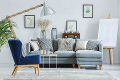 Trendy interior design with sofa. Trendy interior design with gray elegant sofa, navy blue armchair and patterned pillows Royalty Free Stock Photography