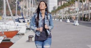 Trendy jaunty young woman enjoying a stroll stock video