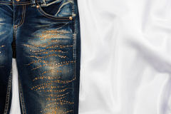 Trendy jeans with rhinestones lies on white silk Royalty Free Stock Photos