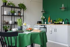 Trendy kitchen with dining table with green tablecloth set for romantic dinner. Concept photo royalty free stock images
