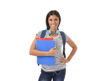 Trendy latin student girl holding notepad folder and book carrying backpack smiling happy Royalty Free Stock Photos