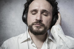 Trendy, listening and enjoying music with headphones, man in whi Stock Photography
