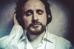 Trendy, listening and enjoying music with headphones, man in whi Royalty Free Stock Images