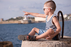 Trendy little boy in sunglasses and vest points finger into distance sitting against sea Stock Photos