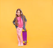 Trendy little girl child listening to music in headphones. Stylish kid girl wearing vibrant modern clothes holding a skateboard over yellow background. Trendy Stock Photography