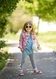Trendy little girl in park with teddybear in hand. With sunglasses Royalty Free Stock Images