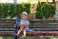 Trendy little girl sitting on a wood bench with her orange handbag Stock Image