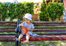 Trendy little girl sitting on a wood bench with her  orange handbag Stock Photography