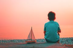 Trendy living coral color concept of the year. Trendy living coral color of year 2019. Child at seaside with a toy sailing boat in two tones royalty free stock photography