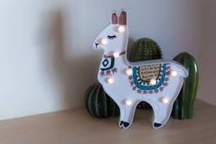 A trendy llama kids night lamp standing on a bedside in dawn or sunrise light with ceramic cactuses behind it royalty free stock image