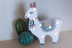 A trendy llama kids night lamp standing on a bedside table in dawn or sunrise light with ceramic cactus behind it royalty free stock photos