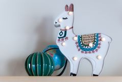 A trendy llama kids night lamp standing on a bedside table in dawn or sunrise light with ceramic cactus and a plastic globe. stock images