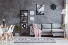 Trendy loft, open dining room. Trendy sophisticated loft living room with open dining space in scandinavian style with gray sofa and wooden table Royalty Free Stock Photography