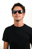 Trendy male model. Portrait of young trendy man wearing sunglasses isolated Stock Photography