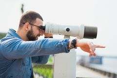 Trendy male person look in binocular telescope points at something Royalty Free Stock Photography