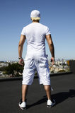 Trendy man from the back. Back view of a trendy young man dressed in white standing on a roof Stock Photo