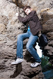 Trendy man climbing in the cave Royalty Free Stock Images