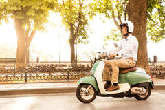 Trendy man driving a scooter in helmet. Sun is shining through trees on background Royalty Free Stock Images