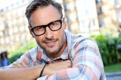 Trendy man with eyeglasses sitting in street Stock Image
