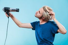 Trendy man with hair dryer. Style and fashion. Young trendy male hairstylist barber with new idea of look changing. Blonde man holding hair dryer and comb stock photography