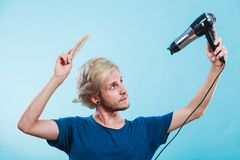 Trendy man with hair dryer. Style and fashion. Young trendy male hairstylist barber with new idea of look changing. Blonde man holding hair dryer and comb royalty free stock photos