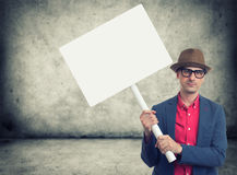 Trendy man holding protest sign. Trendy man holding blank protest sign with copy space stock image