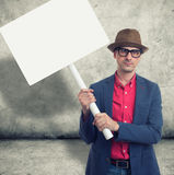 Trendy man holding protest sign. Trendy man holding blank protest sign with copy space stock photo