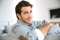 Trendy man at home sitting on sofa smiling Stock Images