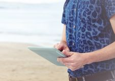 Trendy man mid section with tablet against blurry beach Royalty Free Stock Photos