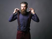 Trendy man pulls suspenders Royalty Free Stock Image