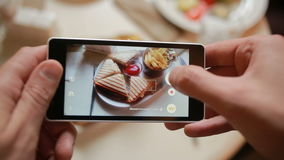 Trendy man in a restaurant make photo of food with mobile phone camera. sandwich stock video footage